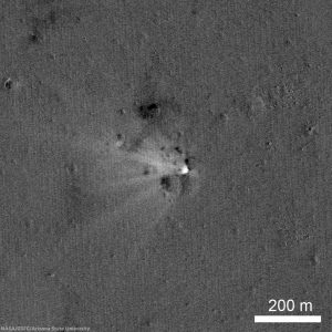 LADEE impact site on the eastern rim of Sundman V crater, the spacecraft was heading west when it impacted the surface. The image was created by ratioing two images, one taken before the impact and another after the impact. The bright area shows the impact point and the ejecta (things that have changed between the time of the two images). The ejecta form a V shaped pattern extending to the northwest from the impact point. Ratio constructed with LROC images M1163066820RE and M1101816767RE [NASA/GSFC/Arizona State University].
